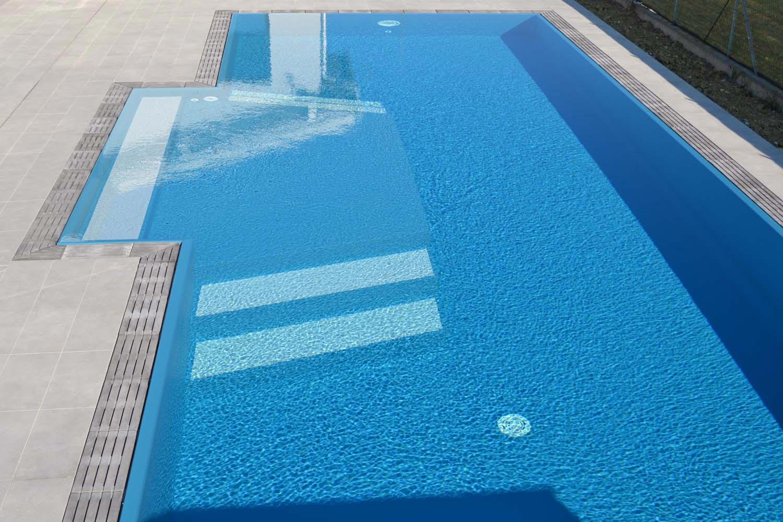 Piscina a sfioro su misura con bagnasciuga interno centrale e rivestimento Sea Blue