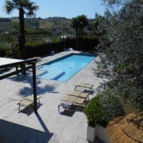 Panorama con piscina interrata a sfioro autopulente. Il liner grigio chiaro si fonde perfettamente con la pavimentazione facendone risaltare l'ampiezza.