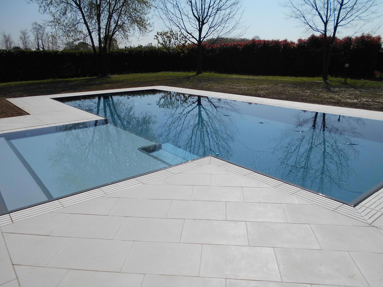 Effetto specchio di una piscina a sfioro perfettamente in armonia con l'ambiente. Struttura isotermica valorizzata dal rivestimento scuso in netto contrasto con la pavimentazione circostante.