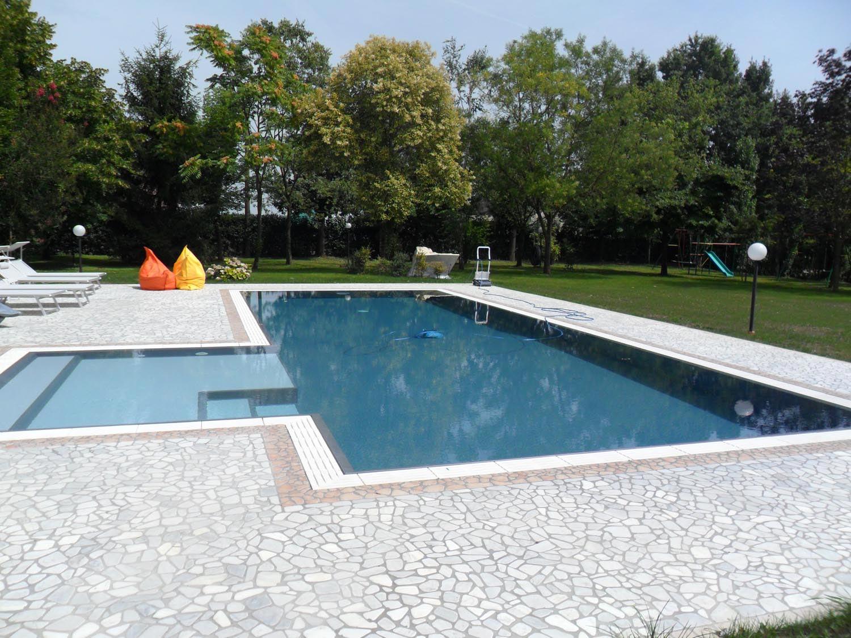 Piscina a sfioro con zona relax laterale esterna caratterizzata da scalini laterali e doppio colore. Il sistema di costruzione Easyblok permette di ottimizzare le forme e adattarle alla propria casa.