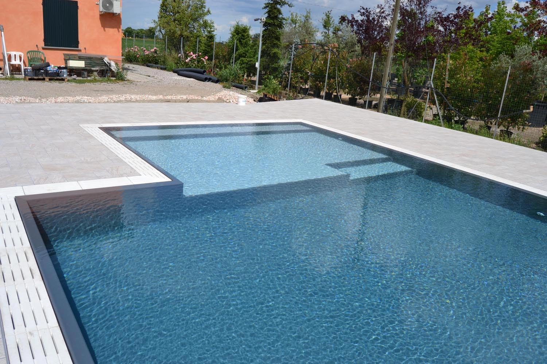 Primo piano ampia spiaggia realizzata in testa a questa piscina a sfioro senza vasca di compenso con rivestimento ad alta pigmentazione grigio scuro.