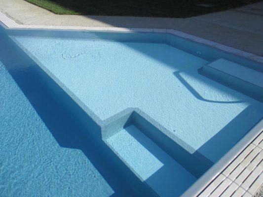 Close up ingresso angolare bicolore di una piscina interrata a sfioro con liner grigio e griglia in pietra naturale bianca.