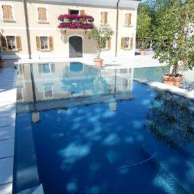 Riflessi di una piscina di design con doppio bordo sfioratore in cristallo. Piscina completamente immersa nell'ambiente circostante grazie alla cascata che permette il passaggio della luce attraverso la vasca.
