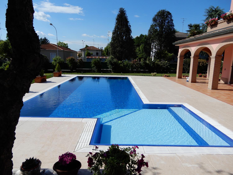 Piscina a sfioro isotermica costruita a Mantova. Ingresso con bagnasciuga angolare a gradini obliqui bicolore.