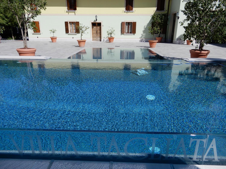Increspature di una piscina a sfioro con cascata in cristallo caratterizzata da un doppio sfioro laterale. Piscina isotermica pulita dal robot piscina Dolphin Maxi.