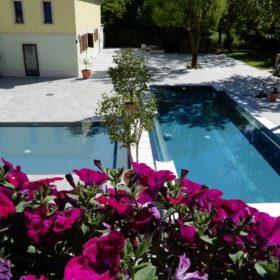 Panoramica piscina a sfioro senza vasca di compenso isotermica ed antisismica realizzata con casseri Easyblok e sistema sfioratore a cascata.