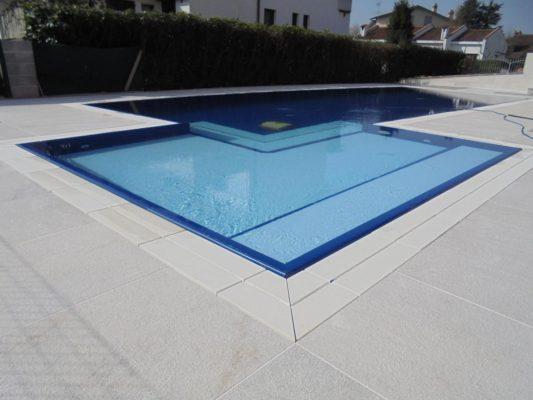 Piscina a sfioro senza vasca di compenso a Modena, progettata con zona relax angolare bicolore per favorire l'ingresso in acqua.