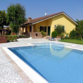Piscina a sfioro Made in Italy con zona relax angolare con scalini interni a trapezio.