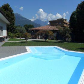 Zona relax con gradini a trapezio di una piscina a sfioro isotermica con liner bianca e bordi in pietra ricostruita bianchi. La scelta della stesso colore rende questa piscina molto armoniosa.