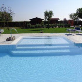 Focus su scalinata d'entrata di una piscina a sfioro isotermica senza vasca di compensazione.
