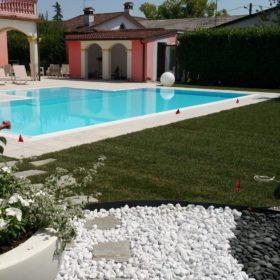 Panoramica piscina a sfioro senza vasca di compensazione con ingresso centrale. Piscina interrata antisismica progettata su misura scegliendo materiali in armonia con quelli della casa.