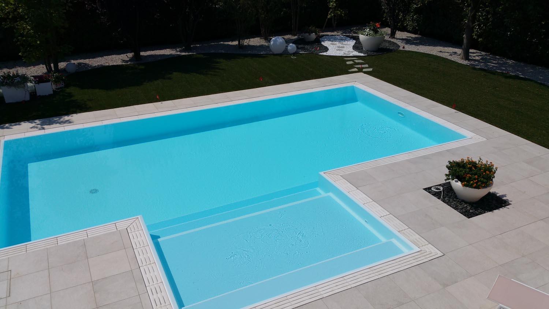 Vista dall'alto delle generose dimensioni di una piscina a sfioro con griglia in pietra naturale.