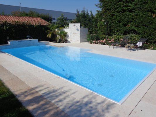 Panoramica piscina a sfioro con cascata in pietra che sovrasta la grande zona idromassaggio con ingresso da zona relax centrale.