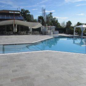 Vista laterale di una piscina a sfioro senza vasca di compenso con doppia zona sdraio angolare con scalini interni. Piscina antisismica con rivestimento grigio chiaro con griglia bianca ad una fessura.