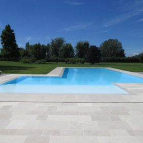 Vista frontale piscina a sfioro con ambia zona relax angolare con ampia area riposo. Le grandi dimensioni dello specchio d'acqua ed il colore chiaro del rivestimento permettono alla piscina di integrarsi perfettamente con l'ambiente circostante.