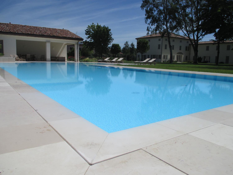 Primo piano bordo sfioratore di una piscina interrata senza vasca di compensazione. Il grande specchio d'acqua permette di creare una superficie riflettente che armonizza la vasca.