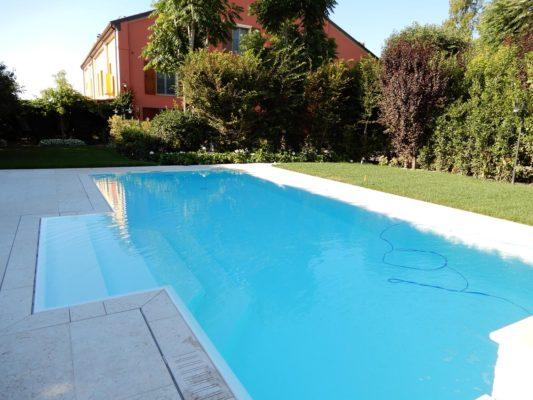 Effetto specchio di una piscina a sfioro con rivestimento bianco e bordo sfioratore a scomparsa. Ingresso centrale con ampi scalini antiscivolo.