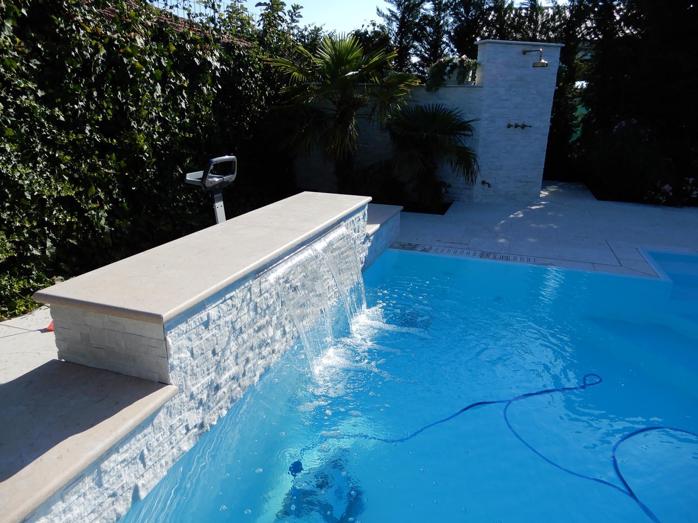 Primo piano cascata laminare piscina interrata a sfioro isotermica ed autopulente. Acqua resa cristallina da impianto di filtrazione ad alto rendimento e robot pulitore Dolphin Maxi a sacco filtrante.