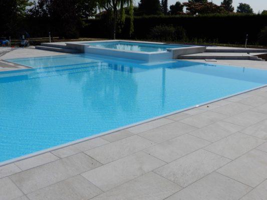 Zona idro sopraelevata a cascata di una piscina a sfioro senza vasca di compenso con rivestimento bianco e bordo a scomparsa.