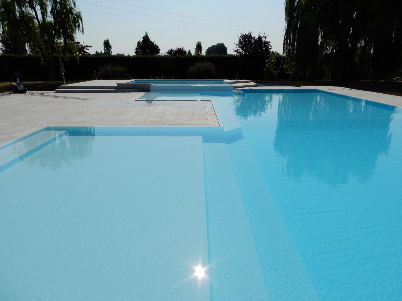 Vista frontale di una piscina a sfioro isotermica autopulente con doppio bagnasciuga ed ampia vasca idromassaggio.