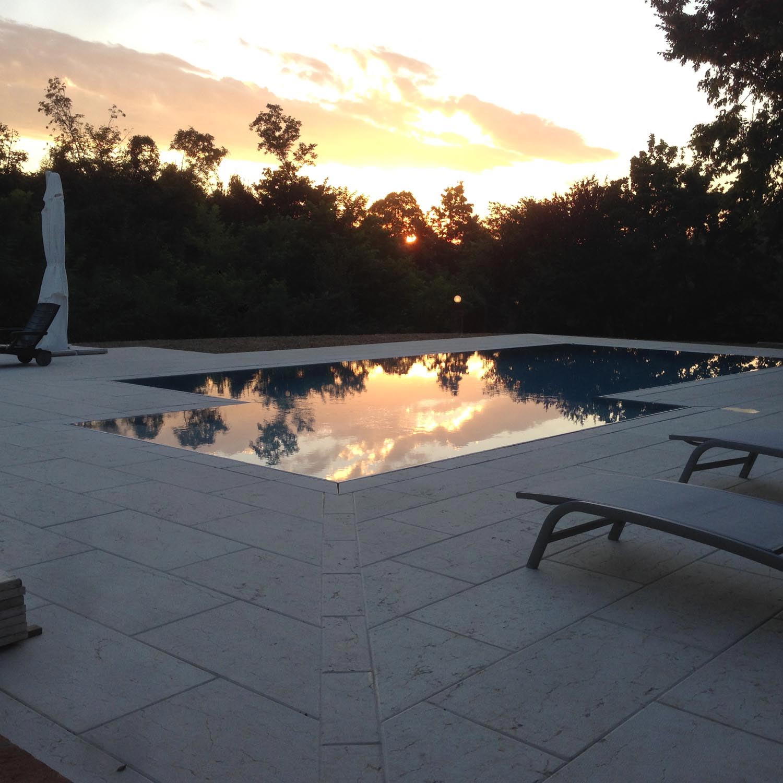 Piscina interrata con bordo sfioratore nascosto che riflette perfettamente l'ambiente circostante. La grande zona relax permette di godersi il tramonto con i piedi in ammollo.