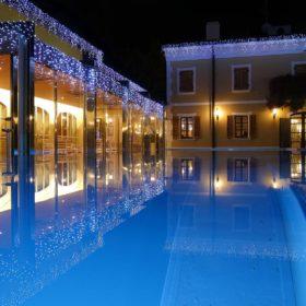 Riflessi notturni di una piscina a sfioro illuminata da luci led ad altissima intensità.