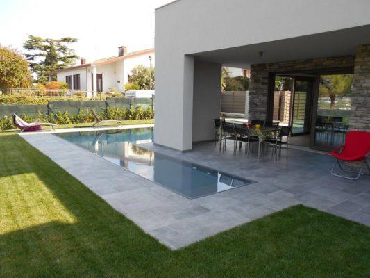 Scala d'ingresso piscina a sfioro di design che circonda la casa. Piscina interrata con bordo sfioratore integrato nella pavimentazione che armonizza la vasca con la casa.