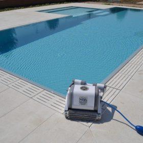 Piscina a sfioro isotermica con rivestimento ad alta pigmentazione grigio chiaro. Piscina interrata sempre in perfette condizioni grazie all'utilizzo del robot pulitore piscina Dolphin Maxi, esclusiva Zavatti.