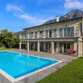 Casa riflessa su piscina a sfioro antisismica con liner bianco e griglia in pietra naturale. Piscina a sfioro con ingresso di design.