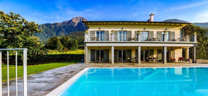 Effetto specchio di una piscina a sfioro isotermica con impianto di filtrazione Made In Italy a sabbia di vetro.