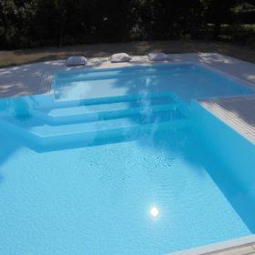 Primo piano zona relax angolare di design con grandi scalini per facilitare l'ingresso in acqua.