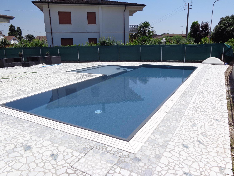 Panoramica piscina interrata con bordo sfioratore in pietra ricostruita bianca. Piscina con ingresso laterale con tappeto materassino di fondo per aumentarne il comfort.
