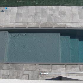 Particolare ingresso laterale di una piscina a sfioro senza vasca di compenso con sfioro a scomparsa.