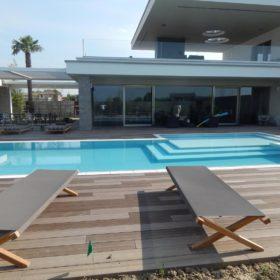 Vista laterale con particolare della spiaggia di una piscina interrata senza vasca di compenso. Piscina costruita in casseri Eps Easyblok antisismici ed isotermici.