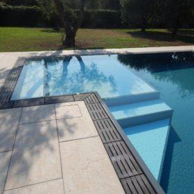 Spiaggia relax angolare bicolore di una piscina a sfioro autopulente e antisismica costruita in casseri Easyblok isotermici.