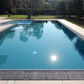 Vista frontale di una piscina interrata a sfioro senza vasca di compensazione ad altissimo risparmio energetico. Piscina interrata con griglia in pietra ricostruita grigia scura in armonia con il rivestimento armato.