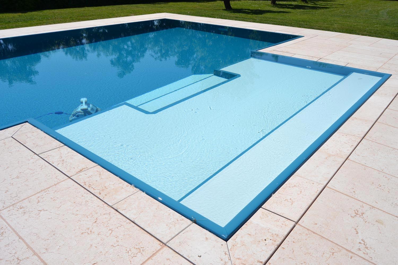 Dettaglio della zona relax di una piscina a sfioro con bordo sfioratore a scomparsa.