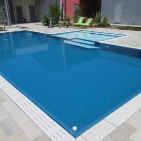 Vista totale di una piscina isotermica senza vasca di compensazione con griglia in pietra ricostruita bianca.