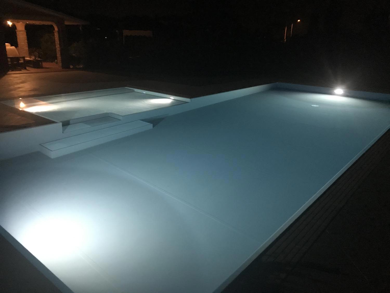 Piscina a sfioro illuminata da lampade led a bassi consumi ed altissima luminosità. Piscina interrata dal design moderno reso ancor più evidente dalla luce bianco ghiaccio.