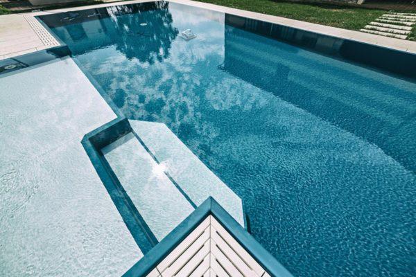 Riflessi di una piscina a sfioro senza vasca di compensazione con liner blu.