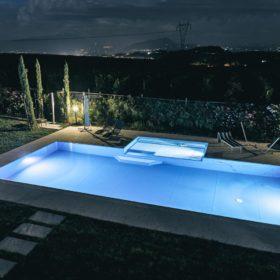 Piscina a sfioro senza vasca di compensazione con rivestimento blu mare, illuminata con lampade led a basso consumo.