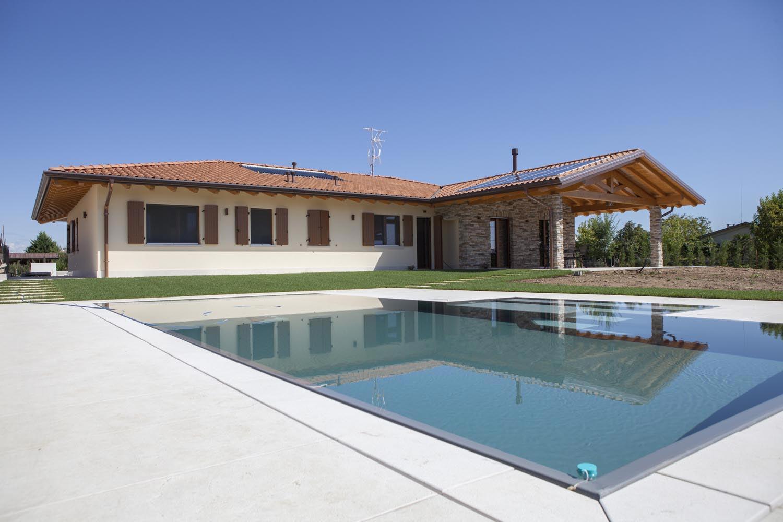 Particolare bordo a sfioro piscina interrata senza vasca di compensazione con rivestimento ad alta pigmentazione grigio scuro.