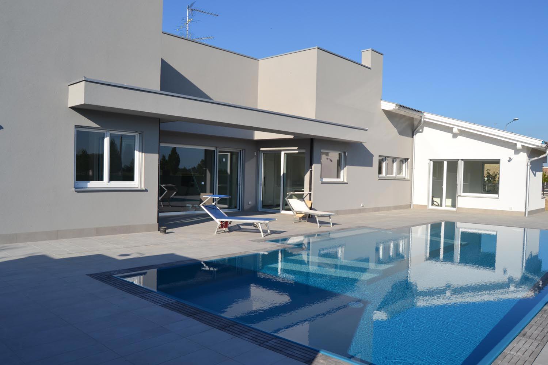 Casa riflessa sulla superficie di una piscina interrata a sfioro integrata perfettamente con l'ambiente circostante.