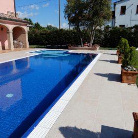 Contrasto tra la pietra ricostruita bianca del bordo sfioratore ed il liner ad alta pigmentazione Sea Blue di una piscina a sfioro isotermica senza vasca di compensazione.