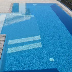 Dettaglio bagnasciuga interno con scalini esterni bianchi. La forma permette di rilassarsi con sdraio o lettino e scendere in piscina in tutta sicurezza grazie al rivestimento antiscivolo.