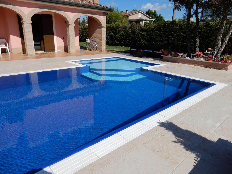 Dettaglio piscina a sfioro senza vasca di compenso con bagnasciuga a scalini chiari. Zona relax completa di luci led a basso consumo e tappeto morbido di fondo.