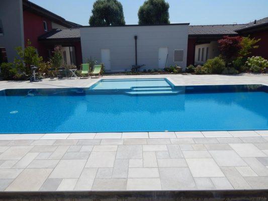 Panoramica di una piscina a sfioro senza vasca di compensazione blu perfetta per il nuoto. Piscina con bagnasciuga centrale perfetto per il riposo.