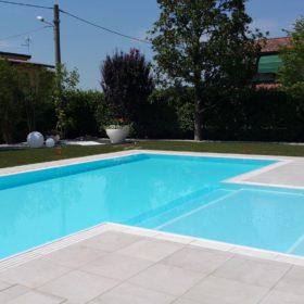 Piscina a sfioro con grande zona relax centrale e griglia in pietra ricostruita bianca. Lo stile sobrio e neutro del liner bianco permette alla piscina di mimetizzarsi e valorizzare il giardino.