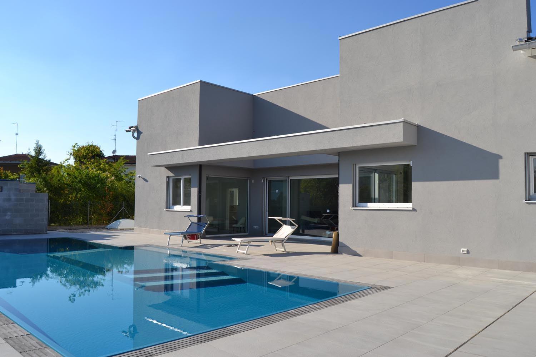 Piscina a sfioro con rivestimento blu e griglia in pietra naturale grigio scuro. La griglia grigia crea un bel contrasto in piscina e si mescola perfettamente con pavimentazione e casa.