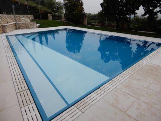 Piscina a sfioro isotermica con rivestimento Sea Blu e scalini longitudinali chiari. La piscina è impreziosita da un bordo in pietra ricostruita che riprende le tonalità chiare della pavimentazione circostante.